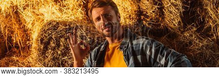 Website Header Of Rancher Looking At Camera And Showing Ok Gesture Near Stack Of Hay