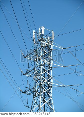 High Voltage Power Lines Intersect At A Large Metal Utility Pole With Cell Tower Against A Blue Sky
