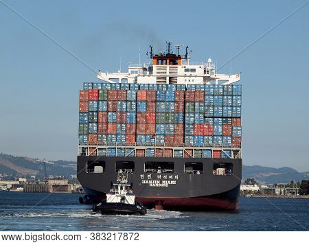 Oakland - August 18, 2010: Hanjin Maimi Hamburg Cargo Boat Is Pushed By Tugboat Out Of Oakland Harbo