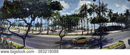 Waikiki - June 9, 2018: Panoramic Of Cars Driving On Kalakaua Ave And People On The Beach.