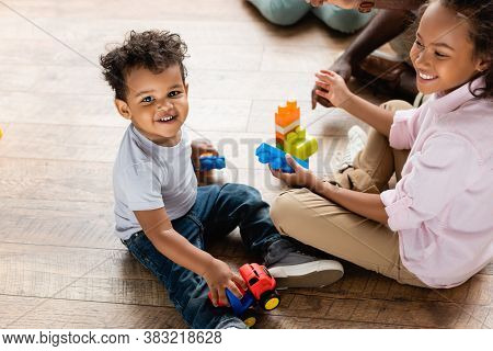 High Angle View Of African American Brother And Sister Playing With Toy Truck And Building Blocks On