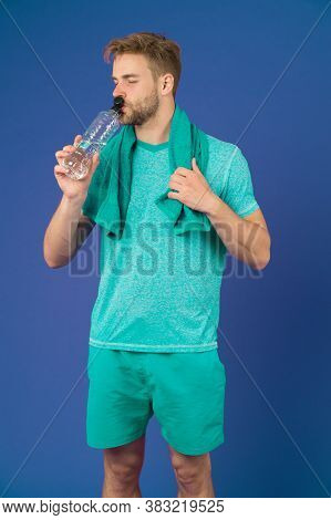 Man Drink Water After Training On Violet Background. Thirsty Sportsman With Plastic Bottle On Purple