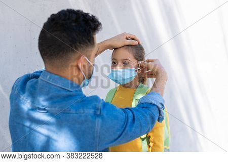 Father Putting Mask To His Daughter Out Of School.