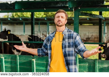 Rancher In Checkered Shirt Looking At Camera While Standing With Open Arms Near Cowshed