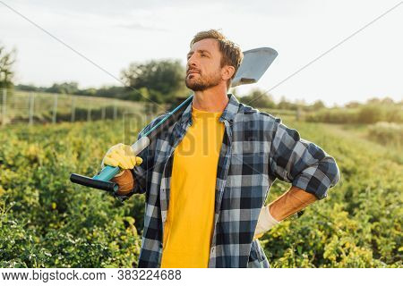 Rancher In Checkered Shirt Looking Away While Standing With Hand On Hip With Shovel In Field