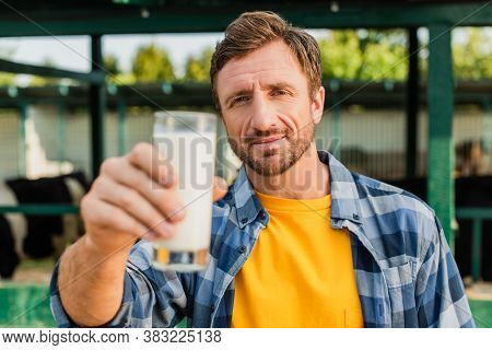 Selective Focus Of Rancher In Plaid Shirt Presenting Glass Of Fresh Milk While Looking At Camera