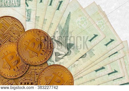 1 Brazilian Real Bills And Golden Bitcoins. Cryptocurrency Investment Concept. Crypto Mining Or Trad