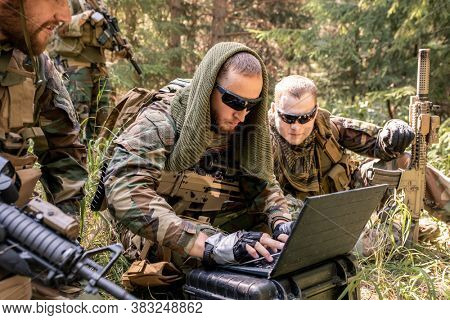 Concentrated army programmer in sunglasses using military computer while getting in touch with military base in forest