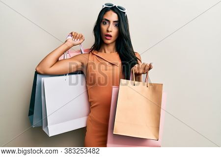 Beautiful hispanic woman holding shopping bags in shock face, looking skeptical and sarcastic, surprised with open mouth