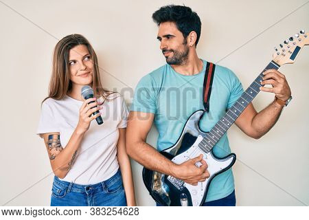Beautiful young couple of boyfriend and girlfriend singing song using microphone and guitar smiling looking to the side and staring away thinking.