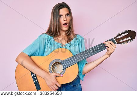 Beautiful caucasian woman playing classical guitar in shock face, looking skeptical and sarcastic, surprised with open mouth