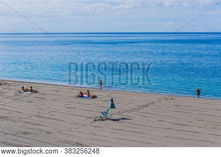 Agua de Pau, Sao Miguel island, Azores, Portugal - August 15, 2020: People at the beach sand in Agua de Pau, Azores. Sao Miguel island, Portugal.