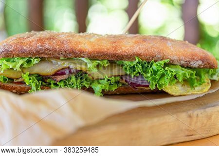 Beef Sandwich With Tomatoes And Lettuce On A Wooden Chopping Board With Ingredients. Ciabatta Bread