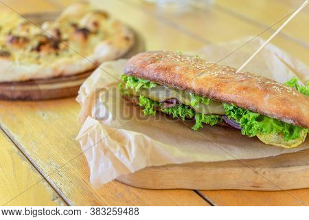 Grilled Beef Sandwich. Ciabatta With Lettuce, Slices Of Fresh Tomatoes, Cucumber, Meat And Cheese.