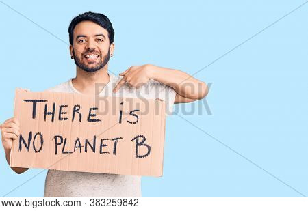 Young hispanic man holding there is no planet b banner pointing finger to one self smiling happy and proud