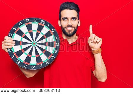 Young handsome man with beard holding dartboard smiling with an idea or question pointing finger with happy face, number one