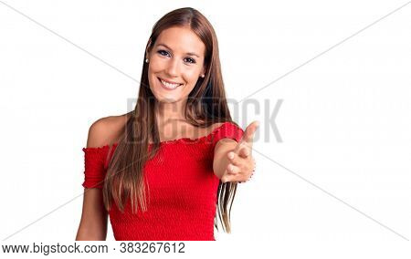 Young beautiful hispanic woman wearing casual clothes smiling friendly offering handshake as greeting and welcoming. successful business.