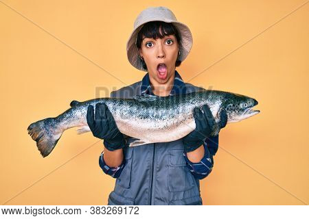Beautiful brunettte fisher woman showing raw salmon in shock face, looking skeptical and sarcastic, surprised with open mouth