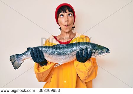 Beautiful brunettte fisher woman wearing raincoat holding fresh salmon making fish face with mouth and squinting eyes, crazy and comical.