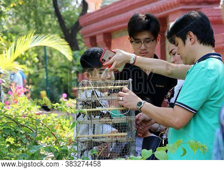 Phnom Penh, Cambodia, Feb 4, 2019 : Parent-child Family Releasing Birds From The Cage For Freedom. T