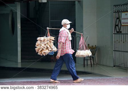 Bangkok, Thailand - Feb 18, 2019 : Fried Pork Skin Seller Walking And Carry With A Carrying Pole At