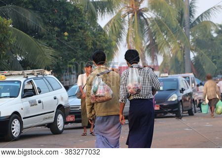 Yangon, Myanmar - Feb 24, 2019 : Two Myanmese Men Walking And Carry The Meat In The Plastic Bag With