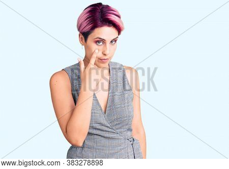 Young beautiful woman with pink hair wearing casual clothes pointing to the eye watching you gesture, suspicious expression