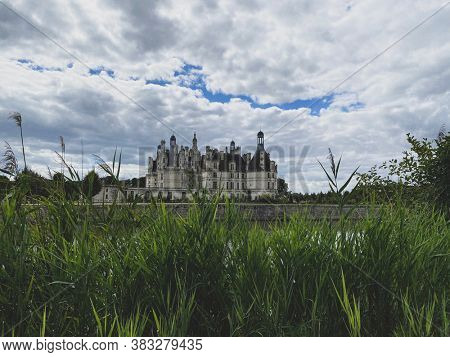 Cloudy view of Chateau de Chambord in the Loire Valley, UNESCO world heritage in France, over wild grass