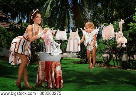 Comic shot of Mom arranged a general wash. A young Housewife washes laundry in a basin. A crying child is dried with clothes and toys on a rope in the garden