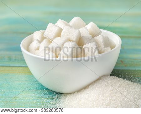 Bowl With Sugar Cubes On A Turqoise Wooden Background
