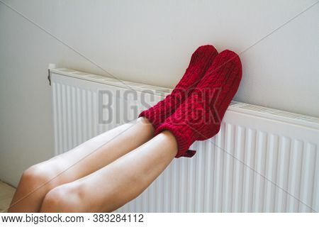 A Young Woman In Warm, Cozy Knitted Socks Warms Her Legs By The