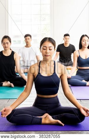 Group of sporty attractive asian people wearing sportswear bra pants practicing yoga lesson on Lotus pose position sitting Padmasana with instructor coach. Work out fitness healthy lifestyle concept