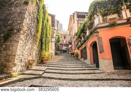 Amazing Old Narrow Street in Bellagio with Shops. Italy. Europe. Famous Picturesque Cobblestone Street with Souvenir Shops, Restaurants and Cafes.