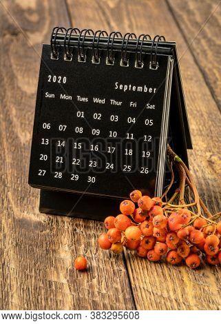 September 2020 - spiral desktop calendar on rustic wood with rowanberry