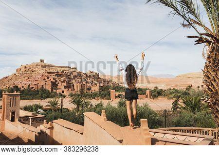 Happy Woman Enjoying Famous Moroccan Landmark Ksar Ait-ben-haddou. View From Behind. Travel In Moroc