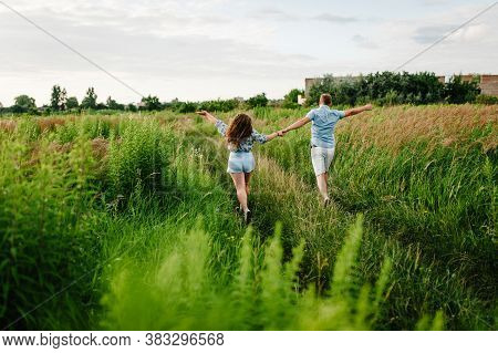 Rear View Of A Romantic Man And Woman Walking On Field Grass, Nature Enjoying Stunning Sunset. Conce