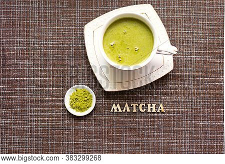 Japanese Matcha Green Tea Is Poured Into A White Mug And On A White Saucer In Powder. Inscription In