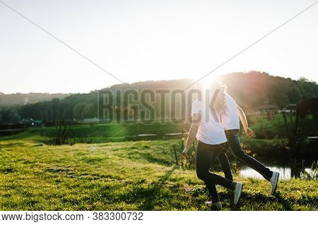 Couple Holding Hands Walking Away. Portrait Of A Romantic Young Man And Woman In Love In Nature. Hus
