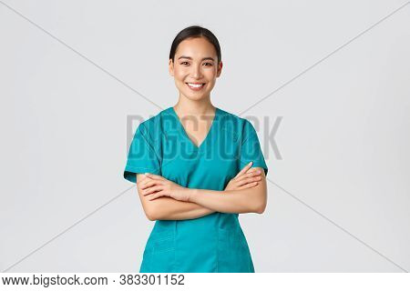 Covid-19, Healthcare Workers, Pandemic Concept. Confident Smiling Asian Doctor, Female Nurse In Scru