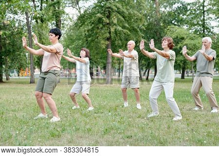 Focused coach raising hands forward while showing relaxing exercise to senior students at qigong practice