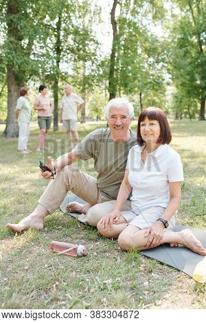 Portrait of positive active senior couple sitting with smartphone on yoga mat in park