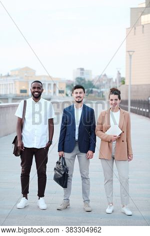 Group of smiling multi-ethnic business school students standing on pedestrian street and looking at camera