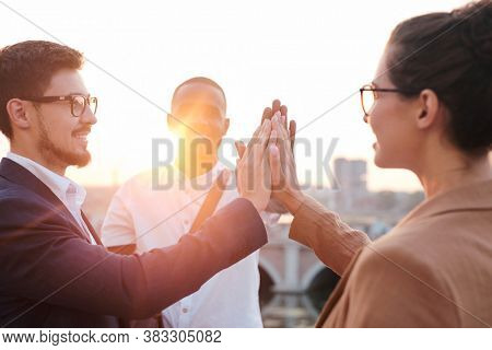 Group of smiling young multi-ethnic business team touching palms together while supporting each other