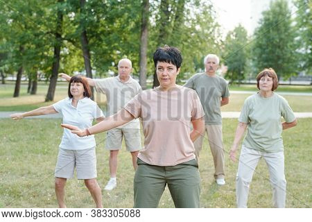 Mature brunette instructor moving arm aside and practicing qigong with senior students in park