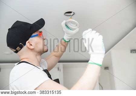 Working Electrician Changes Light Bulb And Installs Wiring For Lamp In Ceiling