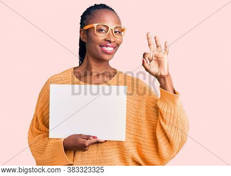 Young african american woman holding cardboard banner with blank space doing ok sign with fingers, smiling friendly gesturing excellent symbol