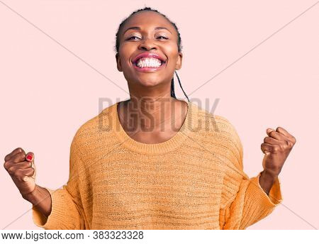 Young african american woman wearing casual clothes very happy and excited doing winner gesture with arms raised, smiling and screaming for success. celebration concept.