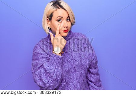 Beautiful blonde plus size woman wearing casual turtleneck sweater over purple background Pointing to the eye watching you gesture, suspicious expression