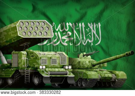 Tank And Missile Launcher With Summer Pixel Camouflage On The Saudi Arabia Flag Background. Saudi Ar