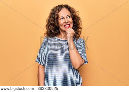 Middle age beautiful woman wearing striped t-shirt standing over isolated yellow background thinking concentrated about doubt with finger on chin and looking up wondering